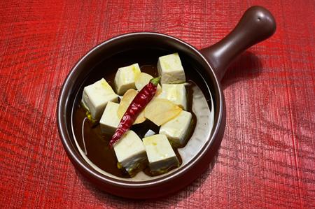 豆腐を一口大にカットし直火可能の耐熱器に並べ入れ、エキストラバージンオリーブオイルを注ぎ入れ、鷹の爪、ガーリックスライスを入れる。